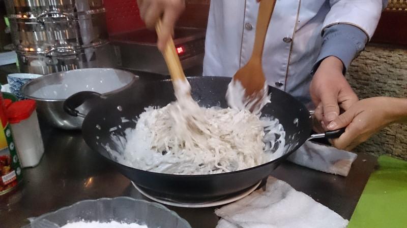 大根もちを中華鍋で炒めている
