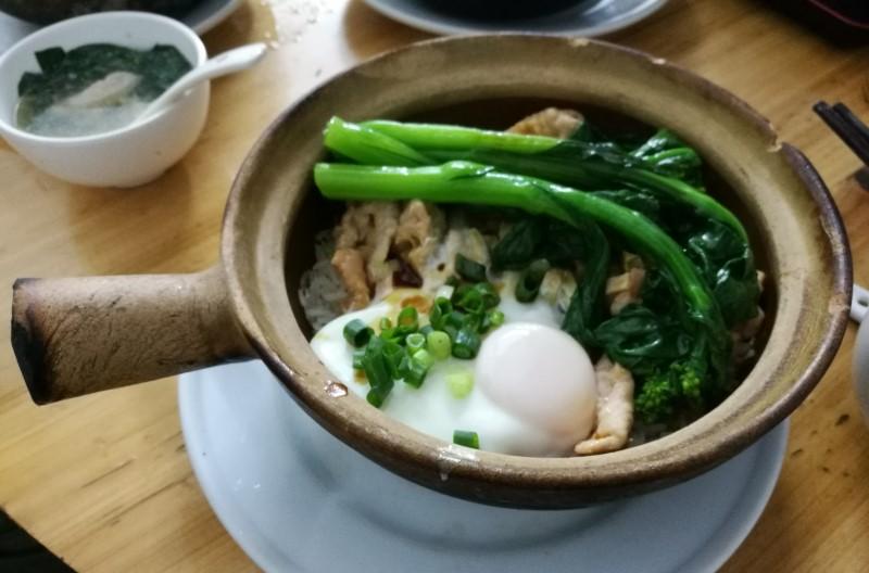 広州の地元名産の料理の土鍋御飯で卵と青菜が乗っている