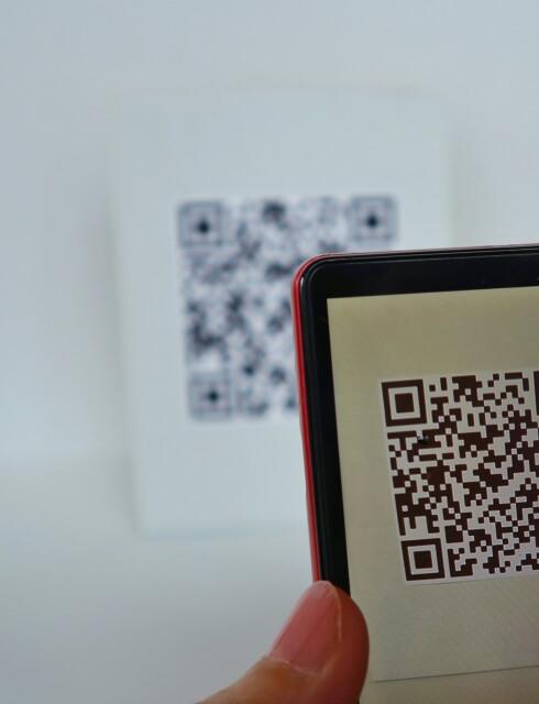 壁にかかっているQRコードをスマートフォンで読み込んでいる