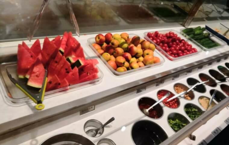 広州市にある四川料理の火鍋の海底撈火鍋のつけダレを作るテーブルに、スイカやネギ、トウガラシなどの調味料や薬味、野菜、果物が並んでいる