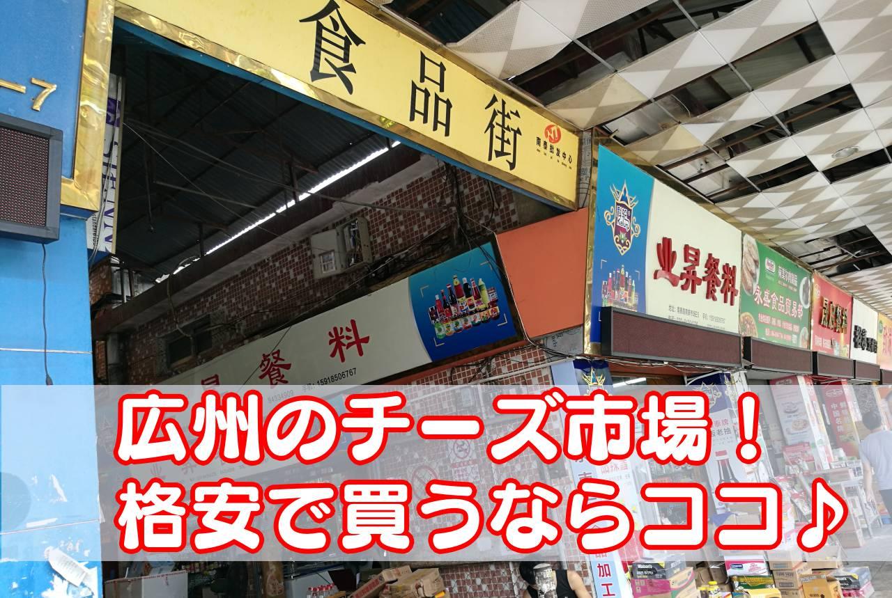 チーズ市場(南泰百贷批发中心)の入り口看板と商店が映っている