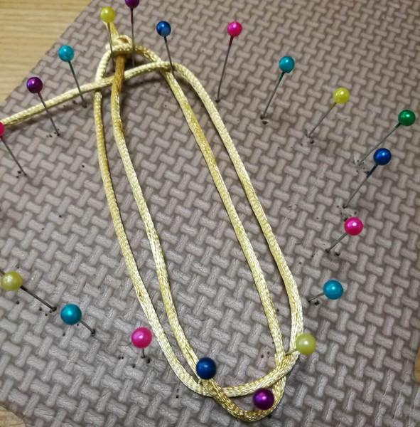 中国紐でコースターを作っている途中で、黄色の中国紐と、待ち針が四角くスポンジに刺さっている