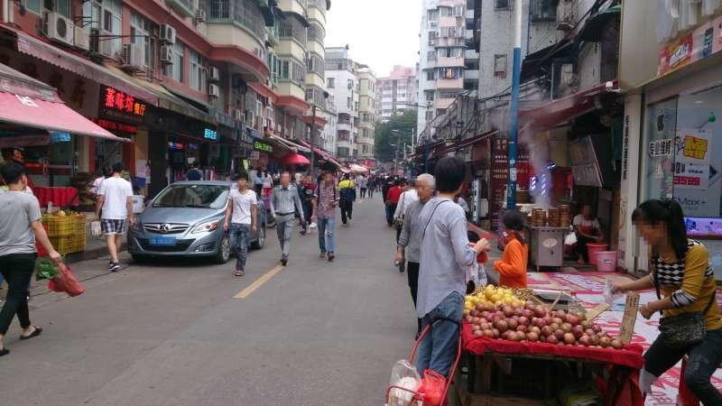 広州の街並みで果物の露店がでたり、道を歩いている人がいる