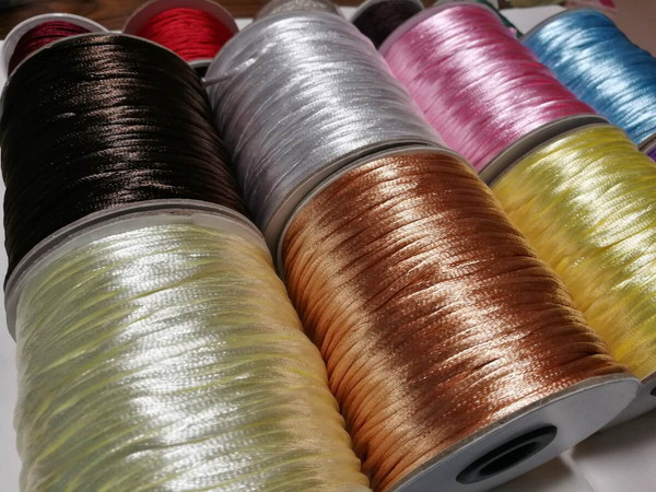 【茘湾】で買った中国紐を並べて撮影している